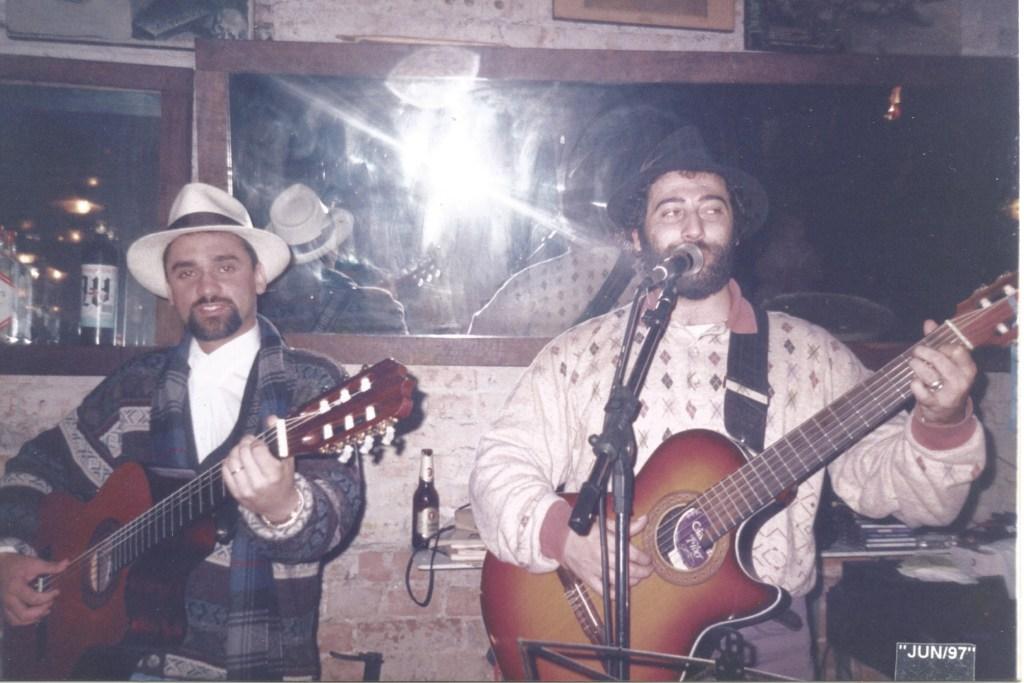 Dois homens de chapéu tocando violão em um palco.